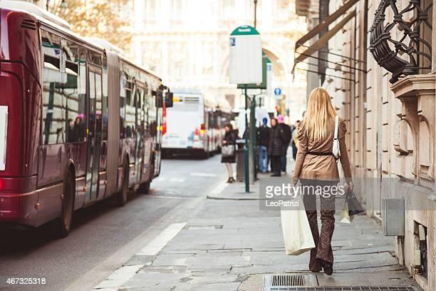 Frau zu Fuß an der Bushaltestelle mit Einkaufstaschen