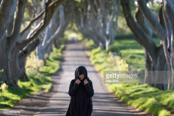 A woman walking at the Dark Hedges