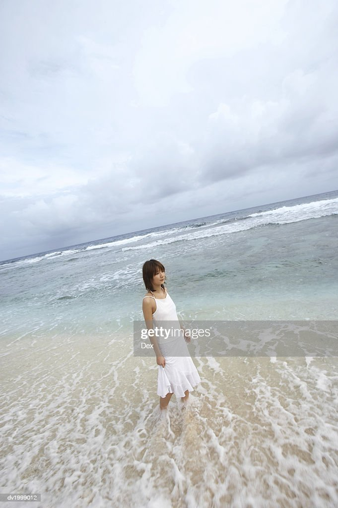 Woman Walking at the Water's Edge on a Beach : Stock Photo