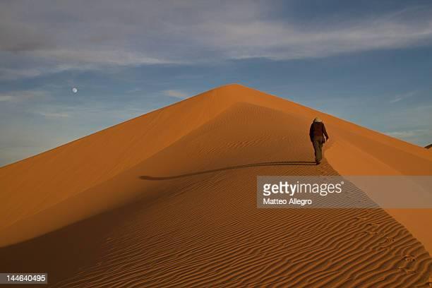 Woman walking away on sand dunes