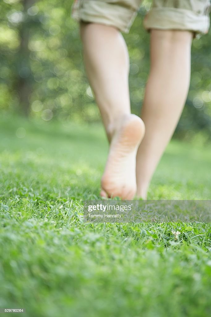 Woman walking bare foot in grass : ストックフォト