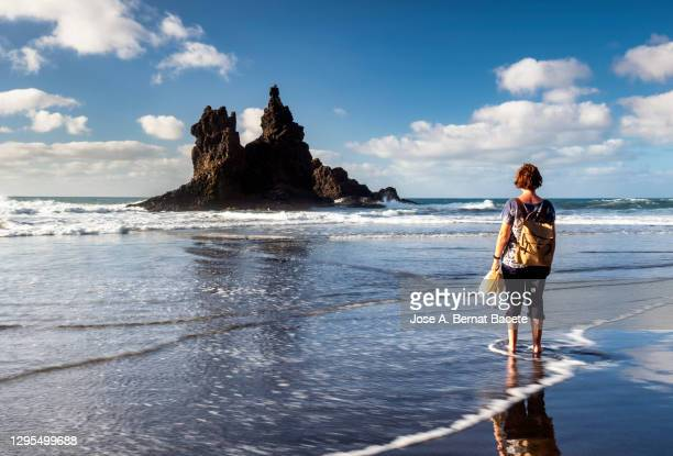 woman walking barefoot along the shore of the beach in a rocky coastline of benijo beach in the canary islands. - atlantic islands stock pictures, royalty-free photos & images