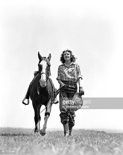 woman walking beside horse holding cowboy hat in gloved hand fashion cowgirl western head on. - cowgirl photos et images de collection