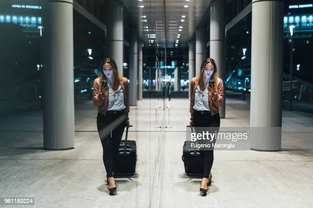 woman walking beside modern building at night, pulling wheeled suitcase, reflection in window - simetria fotografías e imágenes de stock