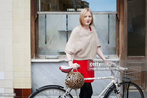 Woman walking bicycle on city street