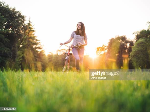 woman walking bicycle on grass - lush stock pictures, royalty-free photos & images