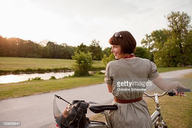 woman walking bicycle on rural road - femme brune de dos photos et images de collection