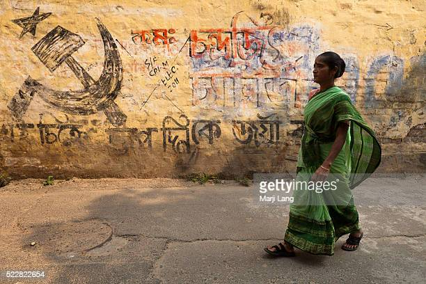 Woman walking by a political Communist symbol near Kalighat in Calcutta West Bengal India Symbol on the wall the Communist Party of India abbreviated...