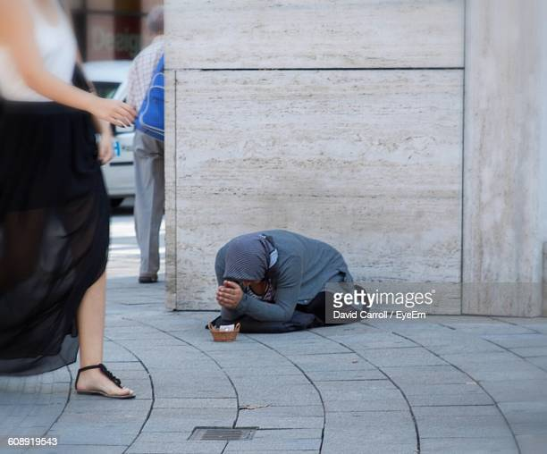 Woman Walking By Beggar On Sidewalk