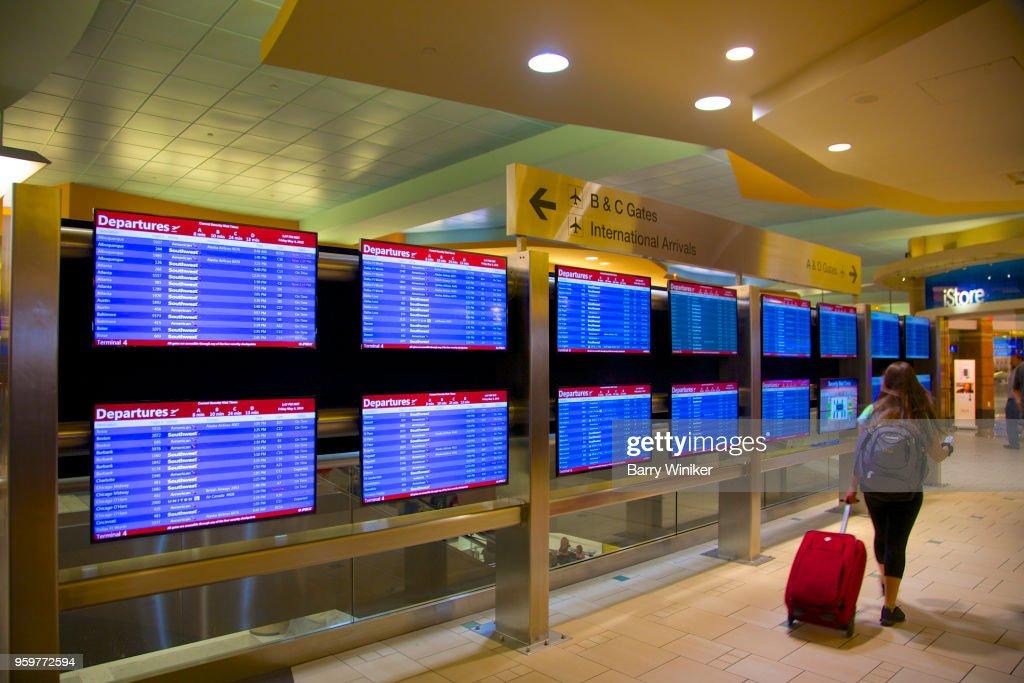 woman walking by flight arrival/departure screens in Phoenix, AZ : Stock-Foto