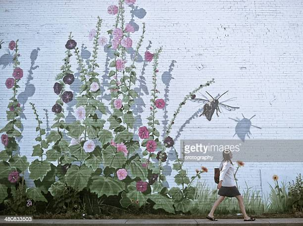 Woman walking by flowery wall