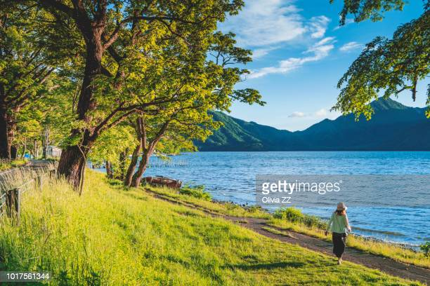 a woman walking by lakeside, lake chuzenji in nikko, japan. - nikko city stock pictures, royalty-free photos & images