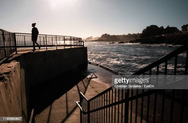 woman walking by railing and sea against sky during sunset - christian soldatke imagens e fotografias de stock