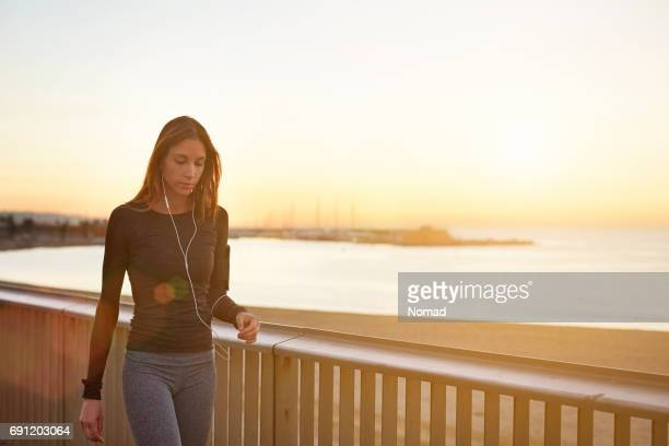 Woman walking by railings at beach during sunset