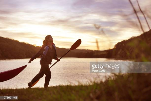 woman walking by river with kayak - one mature woman only stock pictures, royalty-free photos & images