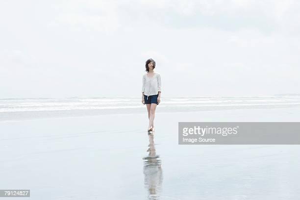 女性は海の散歩 - 浅い ストックフォトと画像