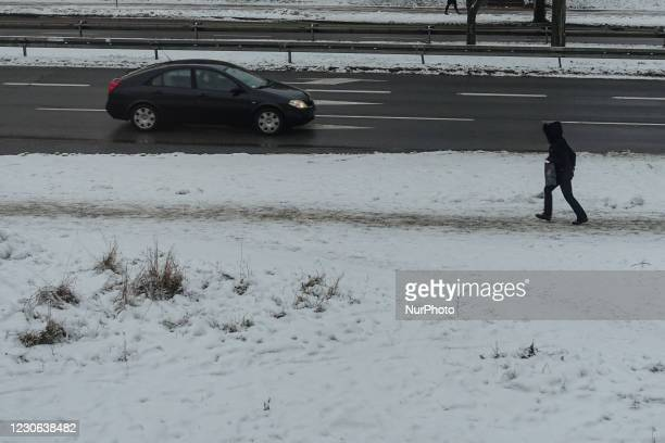 Woman walking by the snowy pavement is seen in Gdansk, Poland on 14 January 2021