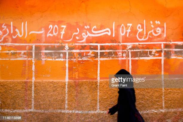 woman walking by wall in market place. - femme marocaine photos et images de collection