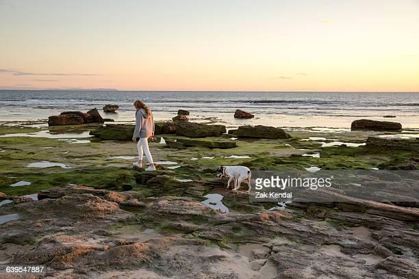 Woman walking dog along rocky beach, Cape of Trafalgar, Spain
