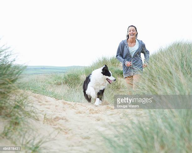 Woman walking dog at beach.