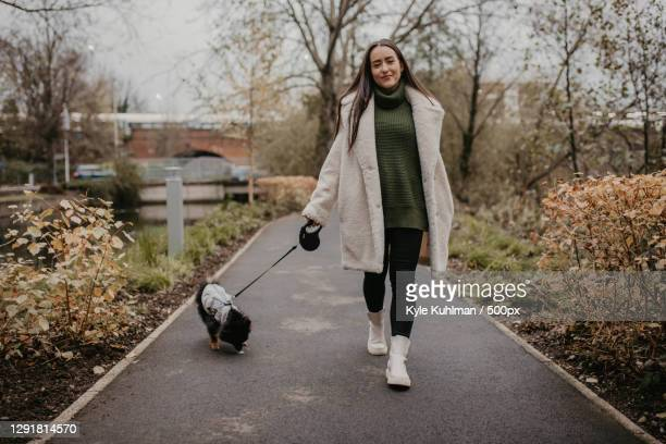 woman walking dog in the park,london,united kingdom,uk - coat stock pictures, royalty-free photos & images