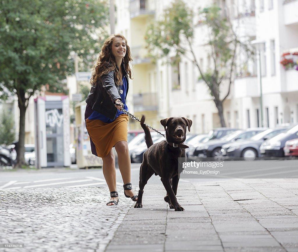 女性の犬のお散歩、街通り : ストックフォト