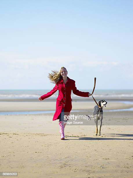 frau zu fuß hund am strand - gummistiefel frau stock-fotos und bilder