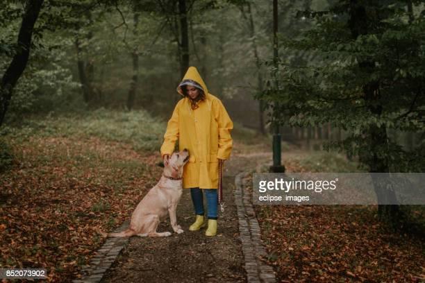 frau zu fuß hund auf misty kalten tag - gummistiefel frau stock-fotos und bilder