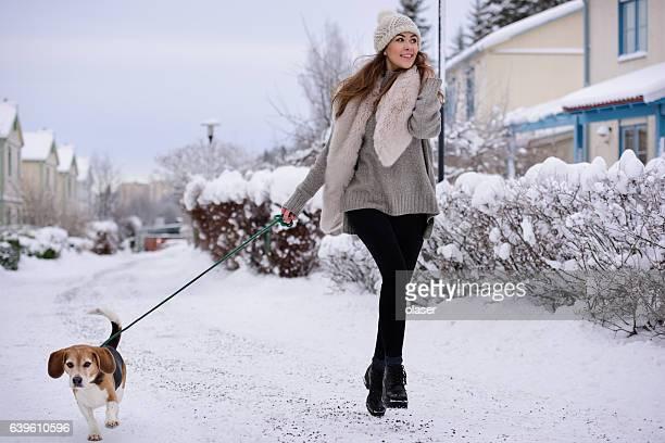 Woman walking (running) dog on winter street