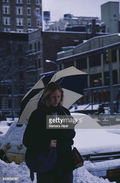 A woman walking down a street in New York City during the blizzard of January 1996