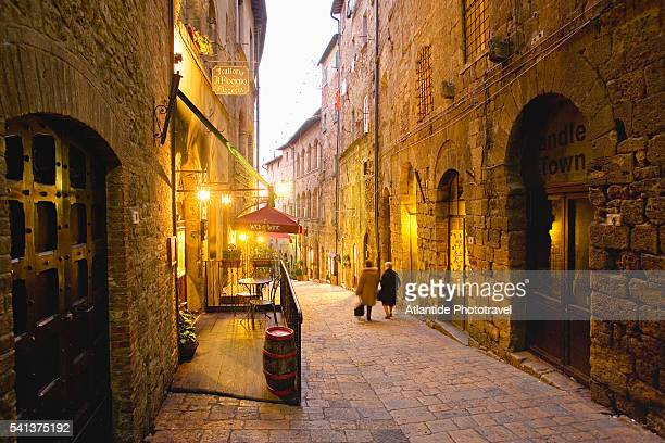 woman walking down alley - volterra stock photos and pictures