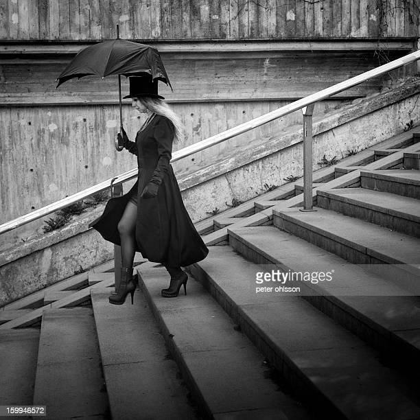 CONTENT] Woman walking down concrete stairs with a broken umbrella and a top hat