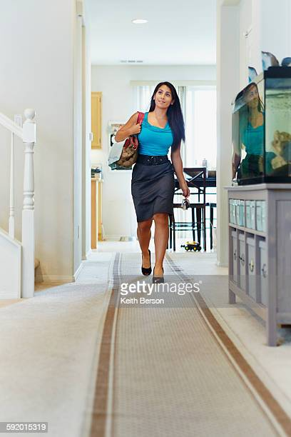 woman walking down hallway of house - down blouse stock photos and pictures