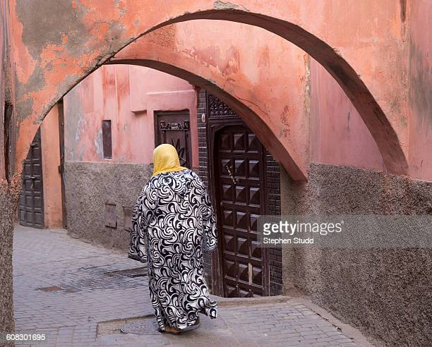 Woman walking down narrow alleyway, old medina