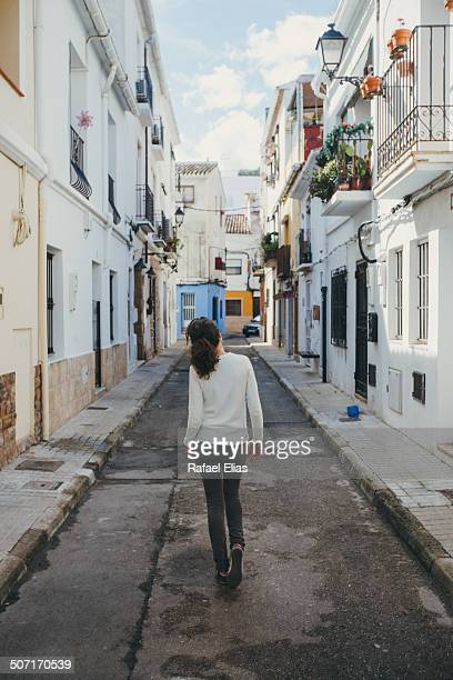 woman walking down narrow street - denia stock pictures, royalty-free photos & images