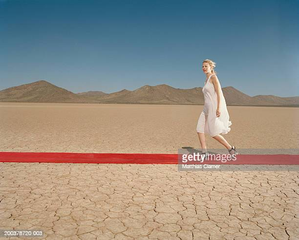Woman walking down red carpet in desert