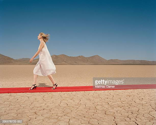 Woman walking down red carpet in desert, smiling, side view