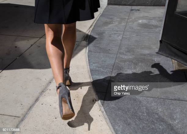 woman walking down sidewalk - gray skirt stock pictures, royalty-free photos & images