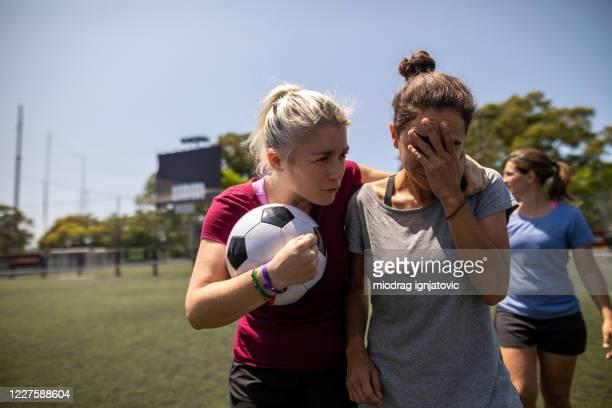 mujer caminando por el campo de fútbol, abrazando y consolando a su amigo después de la pérdida de partido amistoso - fútbol femenino fotografías e imágenes de stock