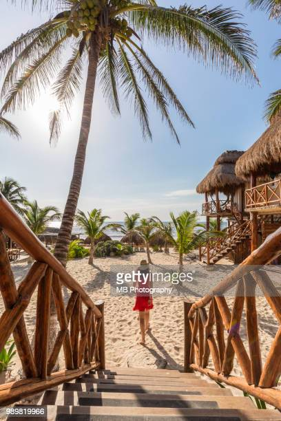 woman walking down staircase in tulum - tulum mexico stock photos and pictures