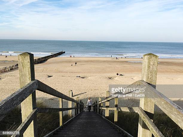 woman walking down stairs at beach - middelburg netherlands stock pictures, royalty-free photos & images