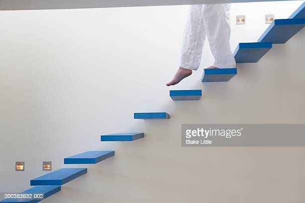 Woman walking down stairs(low section)