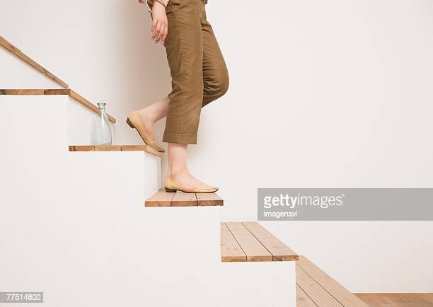 woman walking down stairs - cropped pants stock pictures, royalty-free photos & images