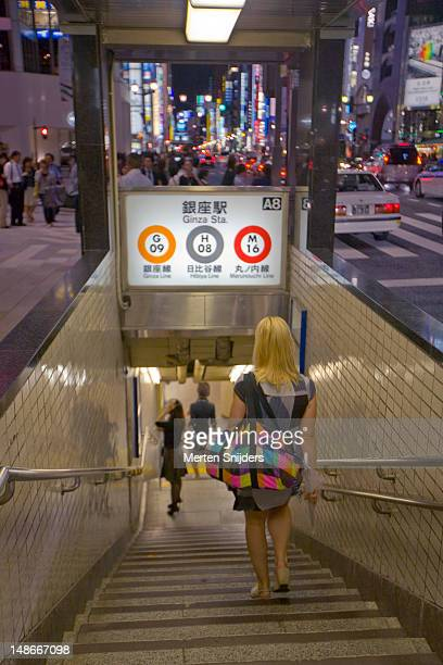Woman walking down stairway leading towards Ginza subway station with city lights in background.