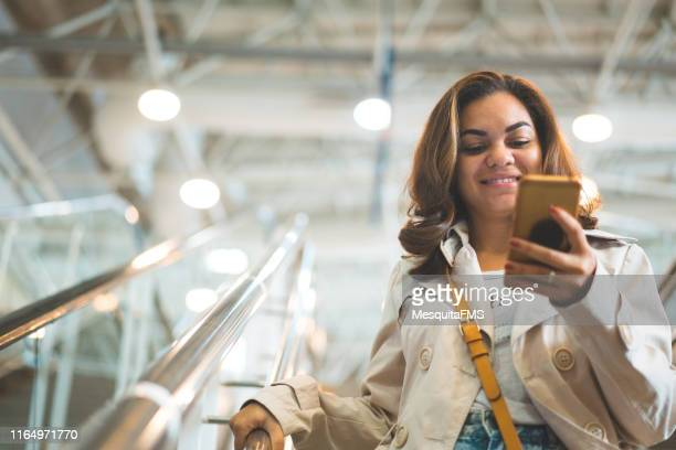 femme marchant en bas des étapes de magasin - femmes d'âge moyen photos et images de collection