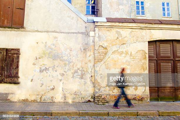 woman walking down street - curb stock pictures, royalty-free photos & images