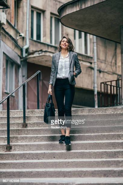 woman walking down the stairs - hands in pockets stock pictures, royalty-free photos & images