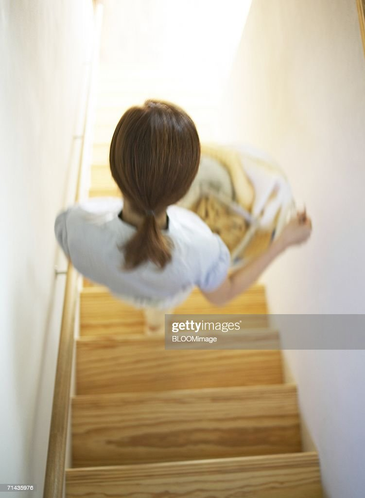 Woman Walking Down The Stairs With A Laundry Basket : Stock Photo