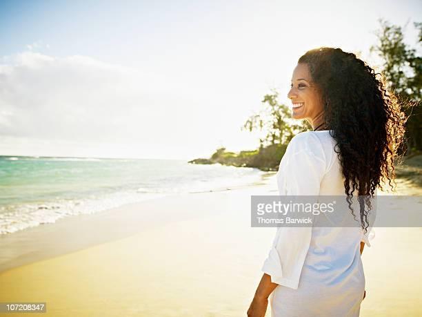 Woman walking down tropical beach smiling