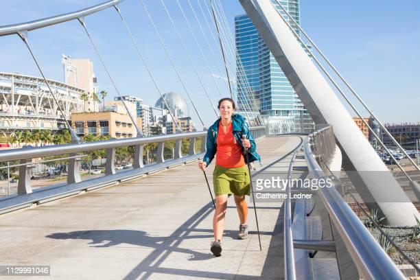 Woman walking energetically across modern city bridge smiling into camera.